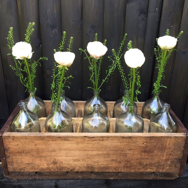 vintage glass water bottles in wooden crate